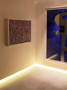 Em vez de recorrer à iluminação pontual, direcionada para as obras de arte, o iluminador fez um rasgo rente ao piso na parede (10 cm de altura x 6 cm de profundidade), com LEDs ocultos pela alvenaria.