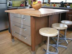 These homeowners combined multiple pieces to create one kitchen island. They found two premade Ikea cabinet units for $500, sandwiched them together then topped it with butcher-block. They found old soda-fountain stools online and had a builder anchor them into the floor joists