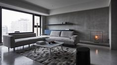 Concrete walls, cement floors, grey tiles, marble and dark stained wood meet in this Taipei apartment by Wei Yi International Design Associates