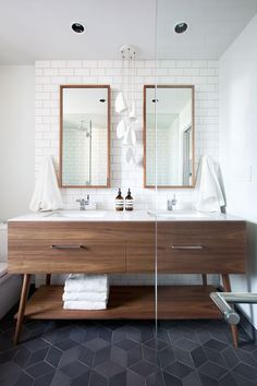 Interior Design by Falken Reynolds - Vancouver loft ensuite bathroom with American Mid Century Modern inspired walnut double vanity, Caesarstone counters, framed recessed medicine cabinets, white subway tile walls, Mutina Ceramics black Tex hexagon tile floors, Bocci 21 pendant, photo by Ema Peter: