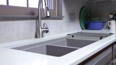 Grey glazed cabinets and trim. Composite sink with integrated drain board. Quartz countertops.