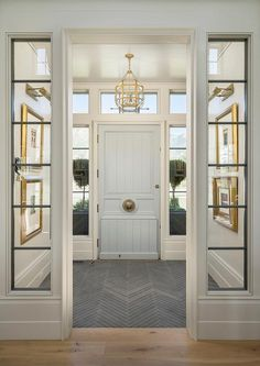 Gray late herringbone floor tiles point to a pale blue shiplap front door framed by sidelights and lit by a  Suzanne Kasler Morris Lantern.