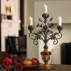IRON FLORAL CANDELABRA  +++   Hand-forged arabesques bouquet candelabra is hand-crafted into a metal floral arrangement display. Each handcut leaf and flower is intricately accented with hand-scrolled ironwork. Use as a beautiful centerpiece for formal dining or as an accent piece in our favorite room. Alderwood base is carved and detailed to resemble a formal vase.