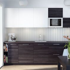 Modern IKEA kitchen with dark worktops and a combination of dark and white cabinet doors