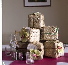"""Favors served as the centerpieces for the simple yet stylish decor. Eight stacked, woven lauhala leaf boxes were adorned with orchids and raffia ribbon and filled with assorted Hawaiian cookies. Each box had a note that read, """"Mahalo for coming and sharin..."""