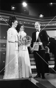 07 January 1969. Eurofashion Final at Shelbourne Hotel. The Irish section of the 1969 Eurofashion Contest judged by John McGuire, Miss Leonora Currie and Mrs Nuala Mc Laughlin. Pictured are winner Colette Dowling (21) Kincora Road, Clontarf,(centre) and model Liz Willoughby, wearing one of Miss Dowling's winning outfits, being presented with 1st prize by George Collly, Minister for Industry and Commerce. the trophy was designed by Patrick MacMahon. #irishphotoarchive www.irishphotoarchive.ie Irish Fashion, Fashion History, Shelbourne Hotel, Photo Archive, 1960s, Centre, Fashion Show, January, Concert
