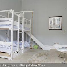 Das Hochbett mit Rutsche und Schaukel macht das Kinderzimmer zum Indoor-Spielplatz. Der helle Teppich mit dem Lammfell und die hellgrauen Wände lassen den Raum …