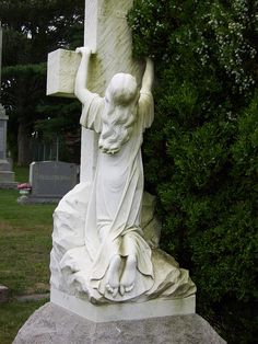 girl clinging cross headstone