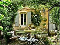 Make your garage side look like a pretty Italian garden....love the rose, shutters and light on the wall.  You could also add a window box.