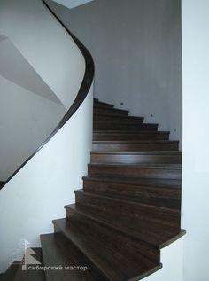 Изящная винтовая бетонная лестница отделана массивом дуба. Гнутые перила повторяют дугу лестницы.