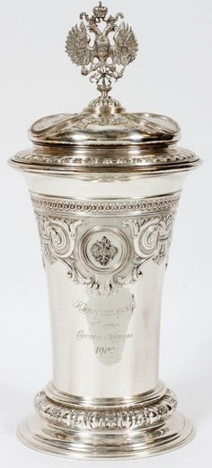 "RUSSIAN SILVER COVERED TROPHY CUP, K. FABERGE, DATED 1902, H 16"", DIA 7"", 'CONCOURS HIPPIQUE', ENCASED:A round trophy cup with tapering sides and flaring base surmounted by a domed cover centered with a crowned double-headed eagle finial; the cover and base are adorned with a total of six round medallions, five of which are portraits of royalty, the sixth a crowned double-headed eagle. Engraved inscription at the front of the cup includes ""Concours Hippique 1902"". The cover is stamped at the…"