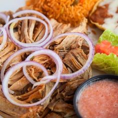 Delight your palate with our Pork Carnitas, a most savory dish, made with pork – which is slow cooked with fresh garlic until fork tender. Topped with red onion rings and served with rice, beans, guacamole and a side dish of fresh mild red sauce. An absolute must try dish!