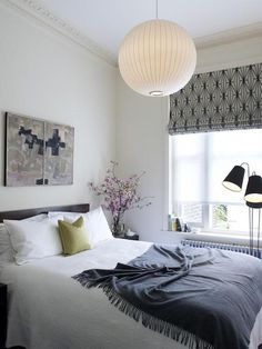 Pendant light (Nelson Bubble Lamp), layered linens, roller shade, floor lamp, white and black. (Photography by Chris Tubbs)