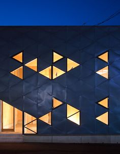 Tessellating windows and cladding panels create a pattern of glowing triangles on the facade of this commercial building in Fukuoka Prefecture, Japan.