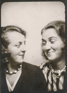 Two women smiling at each other in the photo booth. more like smirking. wonder the story behind it. ;)