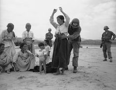 U.S.military policeman searches Korean woman refugee for possible hidden weapons on Naktong River beach in South Korea on Sept. 27, 1950 after U.S. 24th Division drive across the river west of Taegu. Among onlookers in one youngster who obviously needs no search. (AP Photo/Gene Herrick)