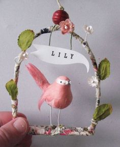 A tiny little captive on a swing.  This bird has been altered by hand with painted eyes and an open beak.  You have the option of getting a little attached word bubble (made of sturdy paper) with an embossed name stamped on it (a great little gift).  Each ornament is handmade, so there are slight variations with each (but consistent integrity!)  This item comes in a gift box.