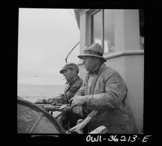 On board a fishing vessel out from Gloucester, Massachusetts. Winch control men intent on seeing to it that the proper amount of cable is let out at the proper spot Photographer Howard Liberman Created September 1942