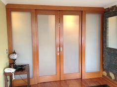Diseño e instalación de puertas correderas en madera de cedro y cristal esmerilado.