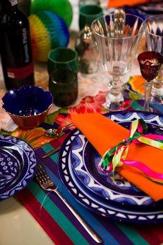 Festiva –  Toalha floral com cores fortes harmonizada com jogo americano também com cores fortes em estampa listrada. Os pratos apresentam vários padrões de estampas em branco e azul. O guardanapo tem ainda uma cor oposta à cor do prato – laranja -, o que fez o conjunto ficar ainda mais alegre.