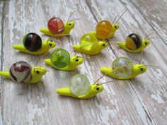Polymer clay snails with Copper wire antennaes  -Glass marble shells  -Black seed bead eyes