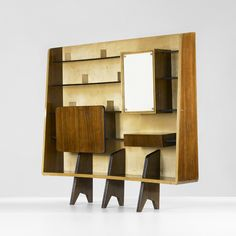 Lot 184: Gio Ponti. bookcase. 1945, Italian walnut, maple, glass, brass. 74¾ w x 13½ d x 69½ h in. result: $20,000. estimate: $20,000–30,000. Bookcase features four shelves, drop-front desk, one drawer and mirrored case concealing a single adjustable shelf.