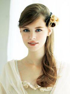 クラシカルなベージュの花コサージュは、ゆるめにカールし、サイドに寄せたダウンヘアに合わせて愛らしく。前髪はサイドに流し、すっきりあけた耳の上...
