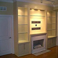 Custom Built-ins Flanking the Fireplace with Glass by Best Cabinets