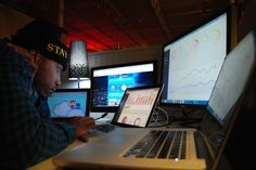 Jovonni Pharr crunches code at Nuracode. This image shows him hunched in front of multiple computer screens.