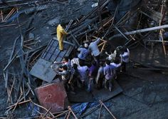 Rescue workers and volunteers search for survivors under the metal debris of a collapsed slab of an under-construction metro rail bridge in Mumbai, September 2012.