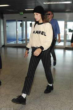 Stylish: Bella looked chic in a Chanel jumper and pinstriped trousers
