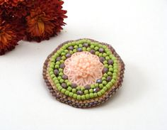 Bead embroidery brooch with resin cabochon.