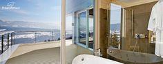 Badezimmer in Hanghaus mit bodentiefen Fenstern und frei stehender Badewanne