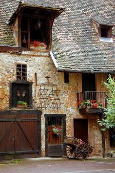 A quiet courtyard in Colmar, France. Living quarters above the farm equipment and animals. The pastures and fields are outside the town.