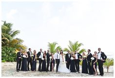 formal bridesmaids in black and groomsmen in tuxedos on beach in Grand Cayman destination wedding