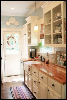 white cabinets, butcher block countertops, farmhouse sink and pretty blue walls kitchen
