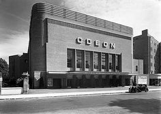 Odeon Cinema, Swiss Cottage, Camden, London, UK.  My local cinema in the 1970s  Oscar Deutsch established the Odeon cinema chain in 1933, and Odeon became a registered trade mark.  His cinemas followed a style, embracing the modern movement and Art Deco, and many were new builds designed by Harry Weedon.  The Odeon in Swiss Cottage was opened in 1937, and is unusual in being of red brick.   Photographer:John Maltby  Date Taken: 1937