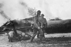 Looking more relieved than triumphant, a pair of Wehrmacht troops trudge past the decapitated turret of a Soviet T-34-76 tank - 1941 - pin by Paolo Marzioli