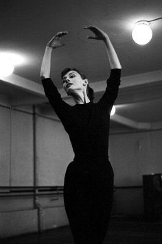 Audrey Hepburn photographed by David Seymour with ballet coach Lucien Legrand, the first dancer and choreographer for the Paris Opera Ballet, at a dance rehearsal for the film 'Funny Face'. Paris (France), 1956.