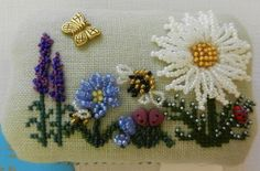 Small rectangular box with a padded lid, linen with beaded flowers in whites and mauves, a beaded bee, butterfly charm and cross-stitch leaves