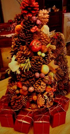 Styrofoam cone filled with various pine cones, brown and red, small apples, leaves, etc.. Small red wrapped boxes to boot