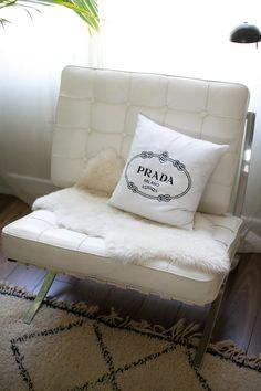 Love the textures! Prada pillow + sheepskin + white leather chair