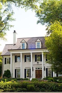 Love this house - Beautiful white house with dormers, black shutters and grand columns framing the wood front door.