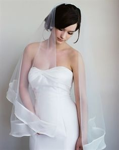 Wedding Veil: Finger-tip length veil features two tiers, silk organza folded trim and tulle.
