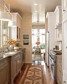 Kitchen, with gray and white - sophisticated earth tones and furniture-style molding warm the slender, galley-style space via Traditional Home magazine.