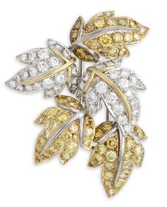 A COLORED DIAMOND AND DIAMOND LEAF BROOCH, 1¾ ins. long, late 20th century, Designed as five leaves set with circular-cut yellow diamonds and diamonds, mounted in 18k white and yellow gold