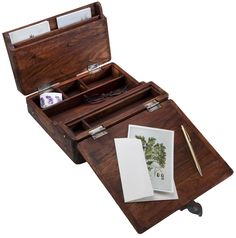 """Campaign Lap Desk. Small, portable campaign desks have been used by generals, scientists, and explorers, in the field and on safari. Made from solid teak with a vintage distressed finish, our campaign desk opens to reveal a sturdy writing surface, numerous compartments for storing papers and writing materials, and an inside drawer for small items. Closed, it measures 10½""""x 8 ¾""""x 3 ½""""d.    $89.95"""