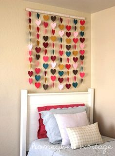 Several strands of colored hearts strung together and hung over a bed