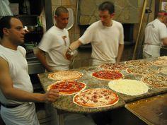 Italy, Rome, Piazza Santa Maria Liberatrice, Pizzeria da Remo, preparing pizzas, blurred motion