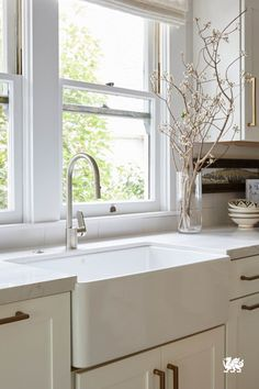 A beautiful white farmhouse sink takes center stage in this monochromatic kitchen. Large windows, white cabinets and our classic Ella™ design keep this kitchen a fresh and timeless.